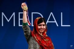 Malala Yousafzai holds up her Liberty Medal during a ceremony at the National Constitution Center, Tuesday, Oct. 21, 2014, in Philadelphia. The honor is given annually to an individual who displays courage and conviction while striving to secure liberty for people worldwide. (AP Photo/Matt Rourke)