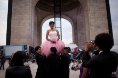 Karine Velazquez is lifted up by members of her court as they pose for photos on her 15th birthday, or quinceanera, at the Revolution Monument in Mexico City, Friday, Aug. 3, 2012. The quinceanera marks a woman's transition from childhood to adulthood and is common in Mexico and other Spanish-speaking countries. (AP Photo/Alexandre Meneghini)