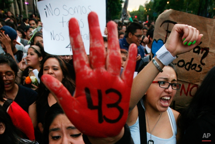 In this Oct. 22, 2014 photo, demonstrators protest the disappearance of 43 students from the Isidro Burgos rural teachers college, in Mexico City. Tens of thousands marched in Mexico City's main avenue demanding the return of the missing students who were rounded up by local police in Iguala, a town in southern Mexico, and handed over to gunmen from a drug cartel Sept. 26. (AP Photo/Marco Ugarte)