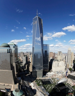 One World Trade Center, center, overlooks the wedge-shaped pavilion entrance of the National September 11 Museum, lower right, and the square outlines of the memorial waterfalls in New York. (AP Photo/Mark Lennihan)