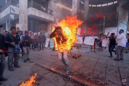 """EDS. NOTE GRAPHIC CONTENT - In this Dec. 5, 2014 photo, farmer Agustin Gomez Perez runs engulfed in flames after he was lit on fire as a form of protest outside the Chiapas state legislature in Tuxtla Gutierrez, Mexico. Perez, 21, was demanding the release of his father, indigenous leader Florentino Gomez Giron, who was arrested last year on charges stemming from a series of demonstrations in 2011 that turned violent. Agustin was taken to a hospital, and his stepmother, Araceli Diaz, said he was """"serious but stable"""" condition with second- and third-degree burns. (AP Photo/Cuartoscuro, Jacob Garcia)"""