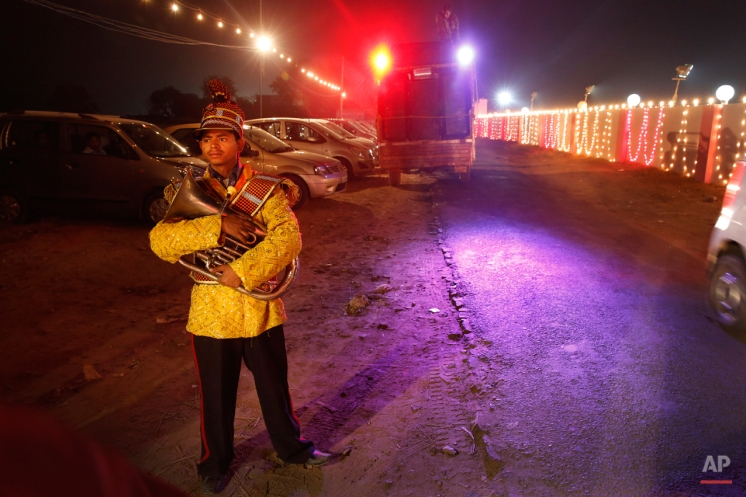 In this Dec. 2, 2014 photo, a member of Indian Brass band, specialized playing in weddings, waits to get back to their barrack after accompanying a wedding procession, in New Delhi, India. (AP Photo/Manish Swarup)