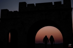 A couple go for a walk as they cross the ancient ''France Gateway'' around of the old city during a dusk winter with cool weather, in Pamplona northern Spain, Tuesday, Dec. 30, 2014. (AP Photo/Alvaro Barrientos)