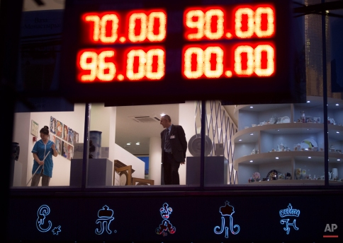 An electronic board shows exchange rates for the Dollar, top, and the Euro, bottom, next to a luxury St. Petersburg china's shop in Moscow, Russia, Tuesday, Dec. 16, 2014. The exchange bureau used the double zero to show the 100 ruble threshold that the euro crossed against the ruble on Tuesday. (AP Photo/Alexander Zemlianichenko)