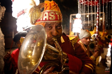 In this Nov. 30, 2014 photo, a member of Indian Brass band, plays trumpet in a wedding procession, in New Delhi, India. (AP Photo/Manish Swarup)