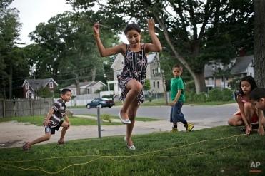 In this July 17, 2014 photo, Maria Ruiz, 9, plays with neighbors in the front yard of her apartment building in Huntington Station, N.Y. Ruiz traveled from Nicaragua to the United States with her sister in June of 2013. Since October 2013, 4,244 minors who crossed Rio Grande River illegally, without their parents, have made New York their home. Metropolitan New York cases are being handled by the federal Immigration Court in New York City, which is struggling to allocate resources, including pro bono lawyers. (AP Photo/Seth Wenig)