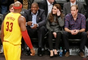 Britain's Prince William, right, and Kate, second from right, Duchess of Cambridge, watch former Houston Rockets player Dikembe Mutombo joke with Cleveland Cavaliers' Brendan Haywood, left, during the second half of an NBA basketball game against the Brooklyn Nets, Monday, Dec. 8, 2014, in New York. (AP Photo/Frank Franklin II)