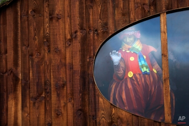 A woman dressed as an elf gestures to children waiting to meet Santa Claus in a Christmas village set up in the medieval castle of Obidos, central Portugal, Wednesday, Dec. 17, 2014. (AP Photo/Francisco Seco)