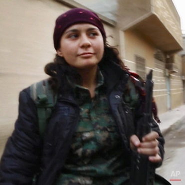 In this image made from a video taken in late November, 2014, Kurdish fighter Pervin Kobani rides in the back of a pickup truck through Kobani, Syria. On the front lines of the battle for Kobani, Kurdish female fighters have been playing a major role in helping defend the Syrian town from an onslaught by the Islamic State extremist group. Pervin Kobani is one of them. She is 19 years old, a farmerís daughter. In late November, she was part of a team holding an eastern frontline position coming under regular attack from extremist fighters trying to take the town since mid-September. (AP Photo/Jake Somkin via AP video)