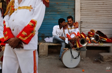 In this Sept. 24, 2014 photo, members of Indian Brass band, specialized playing in weddings, rest on reaching the spot from where the procession is supposed to start, in New Delhi, India. (AP Photo/Manish Swarup)