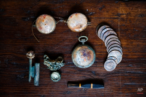 This photo taken on Dec. 17, 2014, shows a lighter, a pendant and its chain, a pocket watch, glasses, coins and a cigarette holder found during the exhumation of a mass grave in Cazalla de la Sierra, Spain. (AP Photo/Daniel Ochoa de Olza)