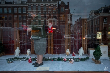 A woman makes an arrangement with Christmas decorations in what used to be a shop window in her house in Amsterdam, Netherlands, Monday, Dec. 8, 2014. (AP Photo/Peter Dejong)
