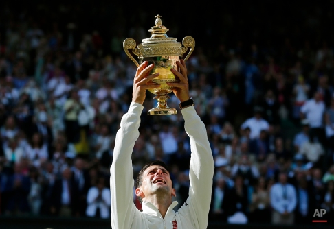 Novak Djokovic of Serbia holds up the trophy after defeating Roger Federer of Switzerland in the men's singles final at the All England Lawn Tennis Championships in Wimbledon, London, Sunday, July 6, 2014. (AP Photo/Ben Curtis)