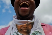 Khanyile Diko cheers while waiting for the motorcade transporting the body of Nelson Mandela in the town of Mthatha on its way to Qunu, South Africa Saturday, Dec. 14, 2013. (AP Photo/Bernat Armangue)