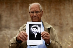 In this photo taken on July 19, 2014, Camilo De Dios, 81, stands in front of the wall in Chaherrero, Spain, where his brother Perfecto de Dios was killed at the age of 19, holding Perfecto's only portrait. (AP Photo/Daniel Ochoa de Olza)