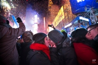 Miranda Echerarria, center left, Christian Prieto, center right, of Niagara, N.Y., kiss at the stroke of midnight during the New Year's Eve celebrations in Times Square, Wednesday, Jan. 1, 2014, in New York. (AP Photo/John Minchillo)