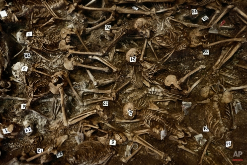 In this photo taken on July 26, 2014, skeletons are numbered on what was a hidden mass grave, during an excavation by the Aranzadi Sciences Society searching for the remains of those killed by their political ideology during and after the Spanish civil war in El Estepar, Spain. (AP Photo/Daniel Ochoa de Olza)