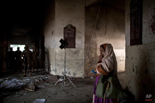 A Pakistani woman looks at the damage inside the Army Public School, attacked Tuesday by Taliban gunmen in Peshawar, Pakistan, Thursday, Dec. 18, 2014. The Taliban massacre that killed more than 140 people, mostly children, at the military-run school in northwestern Pakistan left a scene of heart-wrenching devastation, pools of blood and young lives snuffed out as the nation mourned and mass funerals for the victims got underway. (AP Photo/Muhammed Muheisen)