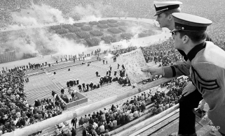 Smoke from colored smoke bombs rises into the air at Philadelphia's John F. Kennedy Stadium, Nov. 28, 1970, as West Point cadets take the field in a parade before the start of the 71st playing of the classic. Looking over the scene as more than 100,000 spectators jam the stadium are Cadet Robert Fitzgerald, left, from New York City, with Navy Midshipman Richard Boeshaar, of Kansas City, Mo. (AP Photo)