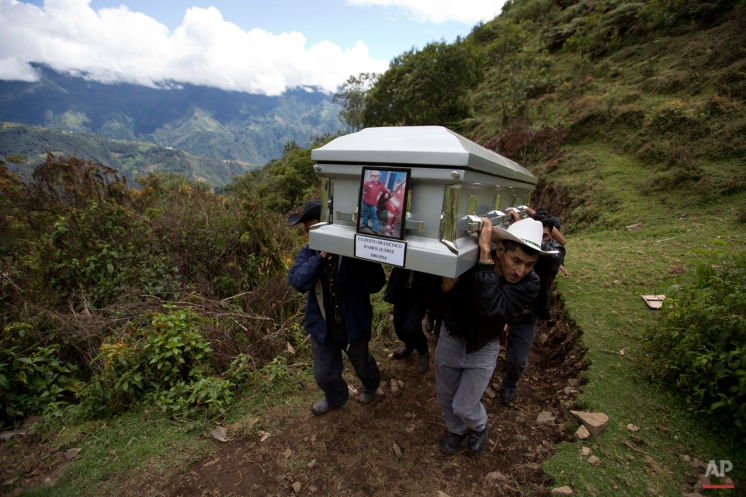 In this July 12, 2014 photo, relatives carry the coffin of Gilberto Francisco Ramos Juarez, a Guatemalan boy whose decomposed body was found in the Rio Grande Valley of South Texas, to a local cemetery in San Jose Las Flores, Guatemala. The 15-year-old Guatemalan migrant was buried in his hometown nearly a month after he became a symbol of the perils facing unaccompanied children who have been flooding illegally into the U.S. (AP Photo/Moises Castillo)