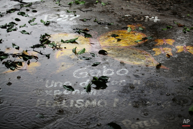 In this April 21, 2014 photo, rain falls on pavement painted with a yellow butterfly in a street where the late Nobel laureate Gabriel Garcia Marquez was born prior to a symbolic funeral ceremony in Aracataca, in Colombia's Caribbean coast. Garcia Marquez died at the age of 87 in Mexico City on April 17. In One Hundred Years of Solitude, the author's masterpiece, clouds of yellow butterflies precede a forbidden lover's arrival. (AP Photo/Ricardo Mazalan)