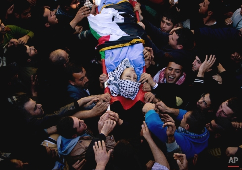 Palestinian mourners carry the body of Palestinian Imam Dwikat who was shot dead by Israeli troops on Monday, in the West Bank village of Baita near City of Nablus , Tuesday, Dec. 30, 2014. The Israeli military said its forces shot and killed Dwika who was throwing stones at drivers in the West Bank. The forces called out to them to stop and fired live rounds into the air to disperse them, then opened fire on the stone throwers when they persisted. (AP Photo/Majdi Mohammed)