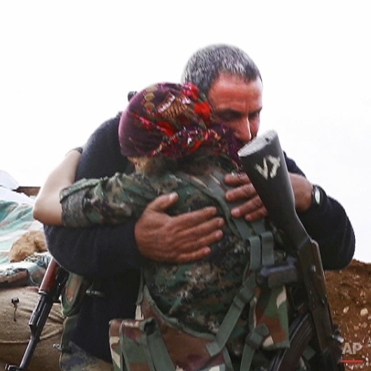 In this image made from a video taken in late November, 2014, Kurdish fighters Pervin Kobani, 19, and her father, Farouk, embrace in Kobani, Syria. On the front lines of the battle for Kobani, Kurdish female fighters have been playing a major role in helping defend the Syrian town from an onslaught by the Islamic State extremist group. Pervin Kobani is one of them. Three weeks ago, Pervin bumped into her father on a street corner. She was surprised to see him holding a gun. She didn't know that he too had decided to fight. She says he is now her comrade first and foremost but hugged him like a father anyway.(AP Photo/Jake Simkin via AP video)