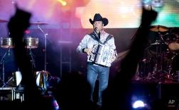 "Lead singer and accordionist Jorge Hernandez of the Mexican norteno band ""Los Tigres del Norte"" performs at the Somos America music festival in Toluca, Mexico, Saturday, Sept. 27, 2014. (AP Photo/Eduardo Verdugo)"