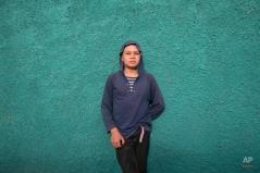 In this Thursday, Nov. 27, 2014 photo, Roberto Castellanos poses for a picture in front of his school in Tegucigalpa, Honduras. (AP Photo/Esteban Felix)