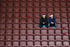 Burnley supporters wearing Christmas hats sit in the stands before the English Premier League soccer match between Burnley and Southampton at Turf Moor Stadium, Burnley, England, Saturday Dec. 13, 2014. (AP Photo/Jon Super)