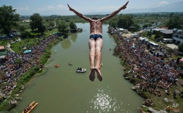Spectators watch as diver Sali Riza Grancina, winner of the competition, performs the winning jump from the Ura e Shenjte bridge during the traditional annual high diving competition, near the town of Gjakova, 100 kms south of Kosovo capital Pristina on Sunday, Aug. 10, 2014. Total of 27 divers from Kosovo competed diving 22 meters high bridge into the Drini i Bardhe river. (AP Photo/Visar Kryeziu)