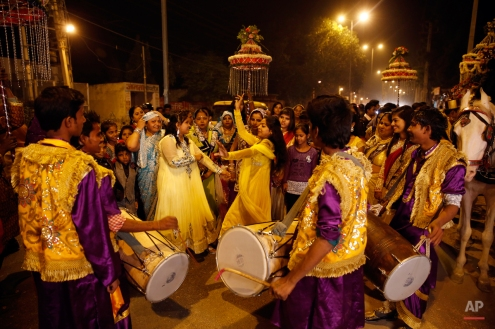 In this Nov. 30, 2014, photo, members of Indian Brass band, play drum or dhol in a wedding procession, in New Delhi, India. The wedding season is in full swing in India, marking what should be the busiest time of year for the traditional brass bands that lead raucous processions announcing the arrival of the bridegroom to the neighborhood. Dressed in faded military-style uniforms or long silken tunics and turbans, brass bands playing the latest Bollywood tunes have long been a must-have at any Indian wedding. But as the tastes of young, wealthier Indians shift to more modern music, young couples increasingly choose DJs playing electronic music instead of live bands. The shift is leaving band owners and musicians struggling to find gigs, exacerbating an already difficult existence. (AP Photo /Manish Swarup)