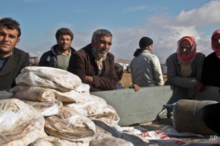 In this Saturday, Nov. 22, 2014 photo, bread is distributed by the Kurdish People's Protection Units (YPG) in Kobani, Syria. The chief baker has a record that there is 3,600+ civilians that need bread daily. One of the few signs of life in this northern Syria border town is the old bakery, brought back online by Kurdish fighters battling the Islamic State group. Closed down for some 20 years, men with the People's Protection Units now work the production line, baking two tons of doughy Arabic bread every day to energize the fighters and feed the spatter of civilians left behind. (AP Photo/Jake Simkin)
