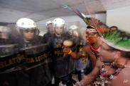 Indians from various tribes argue with police blocking them from entering the Chamber of Deputies where lawmakers are debating the authority to demarcate indigenous lands at Congress in Brasilia, Brazil, Tuesday, Dec. 16, 2014. Brazil's indigenous don't agree with a proposed constitutional amendment that would allow Congress to decide their ancestral land's legal borders, in place of the Ministry of Justice with whom negotiations had already started years ago. Brazilians are legally allowed to watch lawmakers' debate, but police at the scene said they didn't allow the indigenous to enter on suspicion that they would interrupt the debate. (AP Photo/Eraldo Peres)