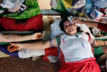 Rosa Caceres, 52, the wife of a former worker of Unicom, a Paraguayan Itaipu Dam contractor, lies on a wooden cross in a symbolic crucifixion in front of the Brazilian Embassy in Asuncion, Paraguay, Monday, Dec. 29, 2014. Caceres is part of a group that for the last 25 years, after the construction on the dam was completed, is demanding compensation benefits from the contractor. The Itaipu hydroelectric dam on the Parana River straddles the Brazil-Paraguay border. (AP Photo/Jorge Saenz)