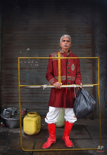 In this Friday, Nov. 28, 2014, photo, Suresh Singh, 60, from Moradabad, some 165 kilometres (162 miles) from Delhi, a members of Master Band, an Indian brass band specialized in playing weddings, poses for a portrait in New Delhi. (AP Photo/Manish Swarup)