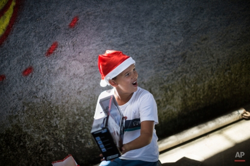 Carlos Eduardo, 8, reacts after getting a remote control helicopter from Santa, exactly what he had asked for in a letter he wrote to Santa and put in the mail, at his school in Rio de Janeiro, Brazil, Wednesday, Dec. 17, 2014. Eduardo said he asked Santa because he knew his parents couldn't afford one. Brazil's postal service organized a visit from Santa as part of their campaign to respond to letters from children addressed to Santa that they find in the mail. (AP Photo/Felipe Dana)