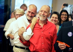 Jefferson Ruck, right, and Thomas Topovski react as they hear they can get a marriage license at the Marriage License Bureau Thursday, Oct. 9, 2014, in Las Vegas. The two were one of the first few couples to get a same-sex marriage license in Las Vegas. (AP Photo/John Locher)