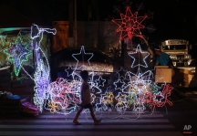 A Filipino boy walks past Christmas decorations for sale in Manila, Philippines on Monday, Dec. 22, 2014. Christmas is one of the most important holidays in this predominantly Roman Catholic nation. (AP Photo/Aaron Favila)