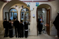 The ultra-Orthodox Jewish Krois family light candles at their home during the Jewish holiday of Hanukkah in Jerusalem's Mea Shearim neighborhood Sunday, Dec. 21, 2014. (AP Photo/Oded Balilty)