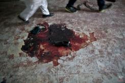 Pakistani men walk past a shoe and blood inside the Army Public School, attacked Tuesday by Taliban gunmen in Peshawar, Pakistan, Thursday, Dec. 18, 2014. (AP Photo/Muhammed Muheisen)