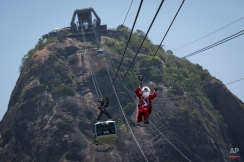A man dressed as Santa Claus descends the Sugar Loaf mountain on a zip line after riding atop the cable car in Rio de Janeiro, Brazil, Thursday, Dec. 18, 2014. (AP Photo/Felipe Dana)