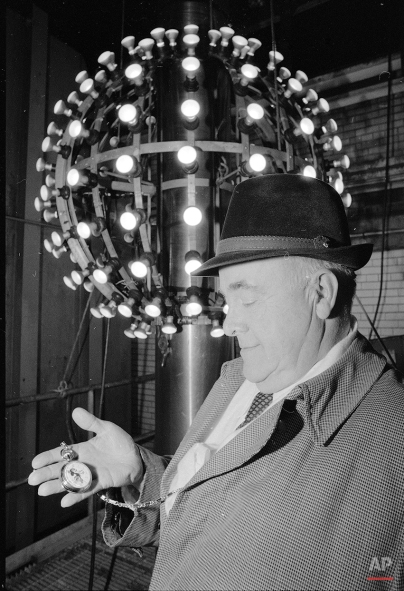 Russ Brown, superintendent of One Times Square, checks his vintage Mickey Mouse watch a few hours bfore the illuminated ball in the background was to be hoisted into position atop the building, Dec. 31, 1980. Brown, who has officiated over the ball dropping for the past 16 years, says he's retiring with the entry of 1981. (AP Photo/David Handschuh)