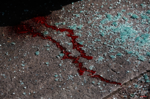 In this March 3, 2014 photo, blood and shattered glass cover the pavement after gunmen opened fire on the driver of a passenger bus, Roger Enrique Hernandez Gutierrez, and his assistant, killing them both in Tegucigalpa, Honduras. Taxi and passenger bus drivers are targets of gangs seeking extortion money in this country with one of the highest murder rates in the world. (AP Photo/Dario Lopez-Mills)
