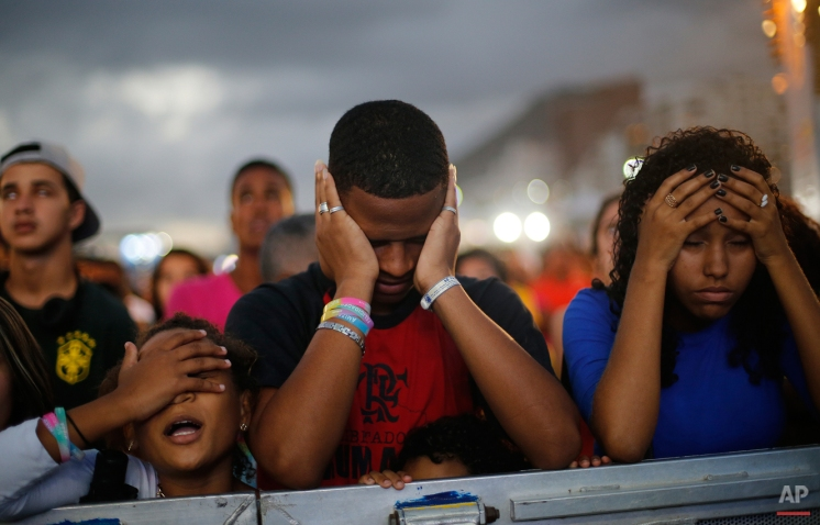 In this July 12, 2014 photo, Brazil soccer fans react in disbelief as their team trails the Netherlands during a live broadcast of the World Cup soccer match, inside the FIFA Fan Fest area on Copacabana beach, in Rio de Janeiro, Brazil. The Dutch beat host Brazil 3-0. (AP Photo/Silvia Izquierdo)