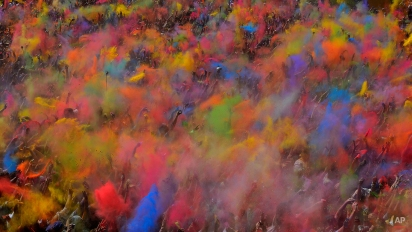 Visitors of the Holi Festival of Colours throw special colored powders in the air in Barcelona, Spain, Sunday, April 6, 2014. The festival is fashioned after the Hindu spring festival Holi, which is mainly celebrated in the north and east of India. (AP Photo/Manu Fernandez)