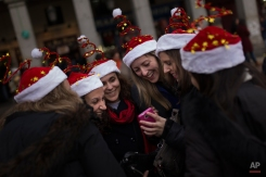 Women wearing Christmas hats check pictures after taking a selfie at Madrid's Christmas market in Madrid, Spain, Saturday, Dec. 13, 2014. (AP Photo/Andres Kudacki)