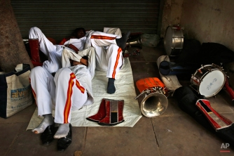 In this Oct. 17, 2014 photo, members of Indian Brass band, specialized playing in weddings, rest on reaching the spot from where the procession is supposed to start, in New Delhi, India. (AP Photo/Manish Swarup)