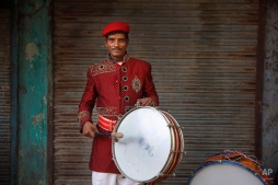 In this Nov. 3, 2014, photo, Chandrashekhar, 32, from Lalitpur, some 547 kilometers (340 miles) from Delhi, a member of Master Band, an Indian brass band specialized in playing weddings, poses for a portrait in New Delhi. (AP Photo/Manish Swarup)