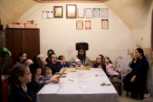 The ultra-Orthodox Jewish Krois family light candles at their home during the Jewish holiday of Hanukkah, in Jerusalem's Mea Shearim neighborhood Sunday, Dec. 21, 2014. (AP Photo/Oded Balilty)